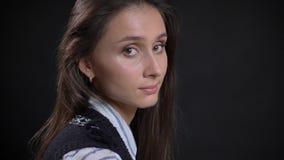 Close-upportret van jong leuk Kaukasisch vrouwelijk gezicht met bruine ogen en donkerbruin haar die draaiend aan de camera kijken royalty-vrije stock afbeelding