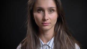 Close-upportret van jong leuk Kaukasisch wijfje die met donkerbruin haar recht camera met gevoelloze gezichts bekijken royalty-vrije stock afbeeldingen