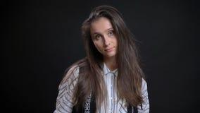 Close-upportret van jong leuk Kaukasisch wijfje met donkerbruin haar die haar hoofd leunen aan de kant en stellen voor stock afbeeldingen