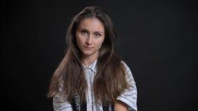 Close-upportret van jong luxueus Kaukasisch wijfje die met donkerbruin haar recht camera met geïsoleerd bekijken stock foto's