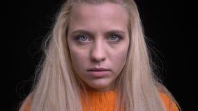 Close-upportret van jong modieus Kaukasisch meisje dat met lang blondehaar recht camera bekijkt stock video