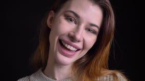 Close-upportret van jong mooi Kaukasisch vrouwelijk gezicht die en met opwinding lachen glimlachen terwijl het bekijken camera stock video