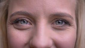 Close-upportret van jong mooi Kaukasisch wijfje die met grijze ogen recht camera met gezichts glimlachen bekijken stock footage