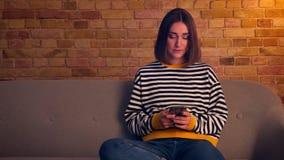 Close-upportret van jong mooi meisje die de telefoonzitting op de laag in een comfortabele flat binnen gebruiken stock footage