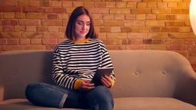 Close-upportret van jong mooi meisje die een videogesprek op de tabletzitting hebben op de bank in een comfortabele flat binnen stock videobeelden