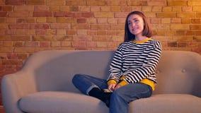 Close-upportret van jong mooi meisje die op een komedie op TV letten die gelukkig zittend op de laag in een comfortabele flat lac stock video
