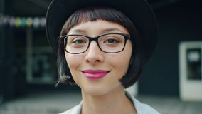 Close-upportret van jong mooi meisje in glazen en hoed die in openlucht glimlachen stock videobeelden