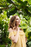 Close-upportret van jong mooi meisje met de krullende kleding van de haarzomer in tropisch bos Stock Afbeelding