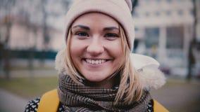 Close-upportret van jong mooi succesvol Kaukasisch freelancermeisje die in de winterhoed het gelukkige bekijken camera glimlachen stock footage