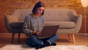 Close-upportret van jong mooi wijfje die online de laptop zitting op de vloer in een comfortabele flat binnen bestuderen stock footage