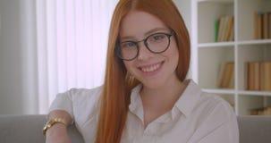 Close-upportret van jong roodharigewijfje in glazen die en camera die met opwindingszitting glimlachen op draaien bekijken stock videobeelden