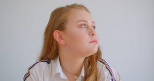 Close-upportret van jong vrij Kaukasisch meisje die camera bekijken die gelukkig binnen in de flat glimlachen stock footage