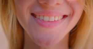 Close-upportret van jong vrij Kaukasisch vrouwelijk gezicht met leuke lippen met het glimlachen uitdrukking stock footage