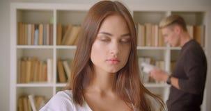 Close-upportret van jong vrij Kaukasisch wijfje dat camera bekijkt die zich in de bibliotheek met een jong mannetje bevindt dat a stock videobeelden