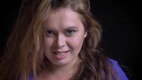 Close-upportret van jong vrij Kaukasisch wijfje die haar mooi donkerbruin haar met charme werpen stock video