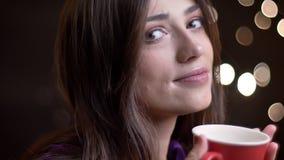 Close-upportret van jong vrij Kaukasisch wijfje met een kop van warme thee die aan camera draaien die en zorgvuldig glimlachen stock video