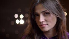 Close-upportret van jong vrij Kaukasisch wijfje met zich haar haar het fladderen het omdraaien en zorgvuldig het glimlachen stock footage