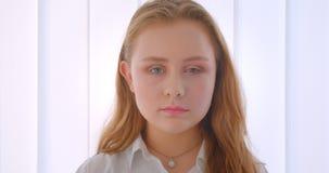 Close-upportret van jong vrij langharig Kaukasisch meisje die camera binnen in de witte ruimte bekijken stock videobeelden