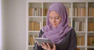 Close-upportret van jong vrij moslimwijfje in hijab gebruikend de tablet en bekijkend camera die zich in bibliotheek bevinden stock footage
