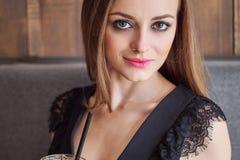 Close-upportret van jonge aanbiddelijke vrouw die met schitterende ogen in make-up grote glaskop van koffie met stro drinken stock foto