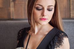 Close-upportret van jonge aanbiddelijke vrouw die met schitterende ogen in make-up grote glaskop van koffie met stro drinken stock fotografie