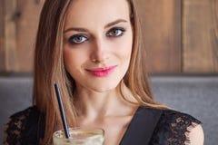 Close-upportret van jonge aanbiddelijke vrouw die met schitterende ogen in make-up grote glaskop van koffie met stro drinken stock afbeeldingen