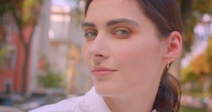 Close-upportret van jonge aantrekkelijke Kaukasische vrouw die camera bekijken die gelukkig het rusten met plezier in park glimla stock videobeelden