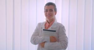 Close-upportret van jonge aantrekkelijke Kaukasische vrouwelijke arts die een boek houden bekijkend camera die zich binnen bevind stock video