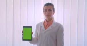 Close-upportret van jonge aantrekkelijke Kaukasische vrouwelijke arts die een tabletand houden die het groene chromascherm tonen  stock footage
