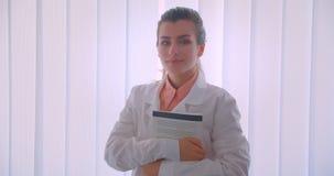 Close-upportret van jonge aantrekkelijke Kaukasische vrouwelijke artsenvakman die een boek houden bekijkend camera status stock video