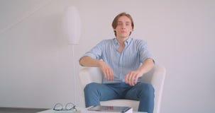 Close-upportret van jonge aantrekkelijke Kaukasische zakenman die camerazitting bekijken in de leunstoel binnen in een wit stock footage