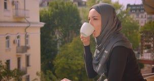 Close-upportret van jonge aantrekkelijke moslimvrouw die in hijab landschap bekijken die zich op balkon van het huis bevinden stock videobeelden