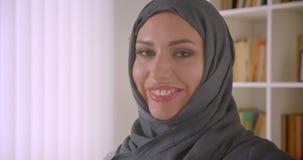 Close-upportret van jonge aantrekkelijke succesvolle moslimonderneemster die in hijab camera bekijken die cheerfully binnen gliml stock video