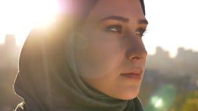 Close-upportret van jonge aantrekkelijke vrouw die in hijab zorgvuldig recht en aan de kanten met zon die bekijken glanzen stock footage