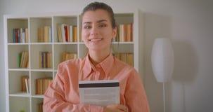 Close-upportret van jonge aantrekkelijke vrouwelijke student die camera bekijken die cheerfully het houden van een boek glimlache stock footage