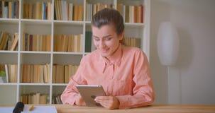 Close-upportret van jonge aantrekkelijke vrouwelijke student die de tablet gebruiken die gelukkig in de universiteitsbibliotheek  stock footage