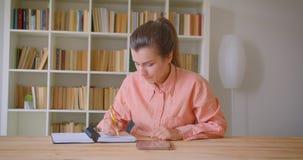 Close-upportret van jonge aantrekkelijke vrouwelijke student die en de tablet in de universiteitsbibliotheek bestuderen gebruiken stock footage