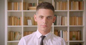 Close-upportret van jonge aantrekkelijke zakenman die camera bekijken die in bibliotheek binnen met boekenrekken glimlachen  stock video