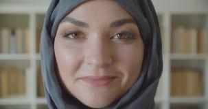 Close-upportret van jonge Arabische aantrekkelijke onderneemster die in hijab camera bekijken die gelukkig in de bibliotheek glim stock video