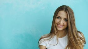 Close-upportret van jonge glimlachende en lachende vrouw die camera op blauwe achtergrond onderzoeken Royalty-vrije Stock Afbeeldingen