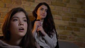 Close-upportret van jonge Kaukasische meisjes die in woonkamer zitten en op TV met groot vermaak letten stock footage