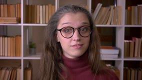 Close-upportret van jonge Kaukasische vrouwelijke student die in glazen met opwinding glimlachen die camera in de universiteit be stock footage