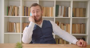 Close-upportret van jonge Kaukasische zakenman die een telefoongesprek op de werkplaats binnen met boekenrekken op hebben stock video