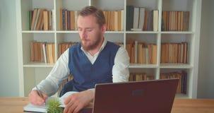Close-upportret van jonge Kaukasische zakenman die laptop in het bureau binnen met boekenrekken op met behulp van stock video