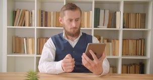 Close-upportret van jonge Kaukasische zakenman gebruikend de tablet en tonend het groene scherm aan camera in het bureau stock videobeelden