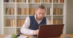 Close-upportret van jonge Kaukasische zakenman gebruikend laptop en binnen nemend nota's over de werkplaats met stock footage