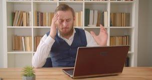 Close-upportret van jonge Kaukasische zakenman gebruikend laptop en wordend gefrustreerd wegens fout in het bureau stock video