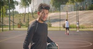 Close-upportret van jonge knappe Afrikaanse Amerikaanse mannelijke de holding van de basketbalspeler bal en in openlucht het beki stock videobeelden