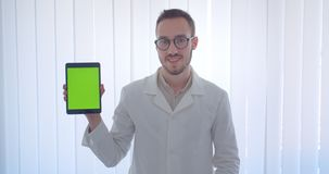 Close-upportret van jonge knappe Kaukasische mannelijke arts die een tablet houden en het groene scherm tonen aan camera in stock video