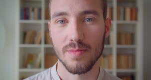 Close-upportret van jonge knappe Kaukasische mannelijke student die camera bekijken die gelukkig in de universiteitsbibliotheek g stock video